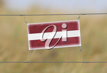 Border fence - Old plastic sign with a flag - Latvia