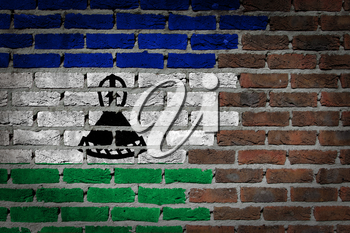 Very old dark red brick wall texture with flag - Lesotho