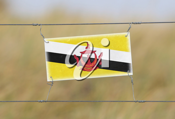 Border fence - Old plastic sign with a flag - Brunei