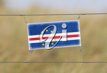 Border fence - Old plastic sign with a flag - Cape Verde