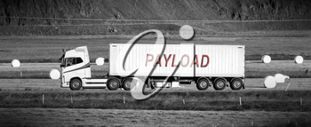 White trruck driving through a rural area - Payload