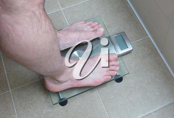Closeup of man's feet on weight scale -