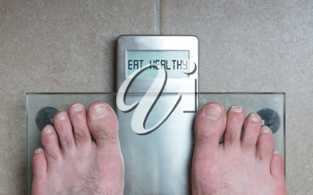 Closeup of man's feet on weight scale - Eat healthy