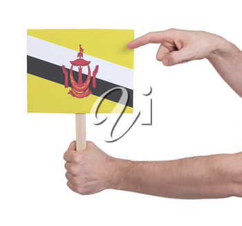 Hand holding small card, isolated on white - Flag of Brunei
