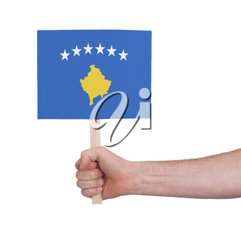 Hand holding small card, isolated on white - Flag of Kosovo