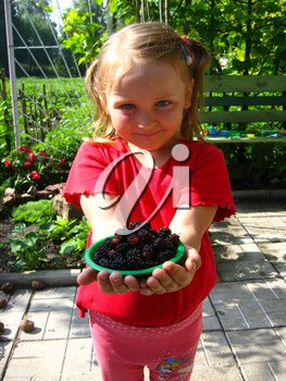 girl offers the plate with ripe black mulberry