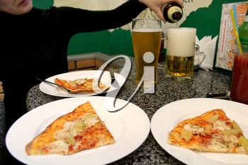 image of woman' s hand pouring beer in a glass and pizza