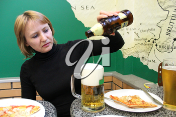 image of woman pouring beer in a glass and pizza