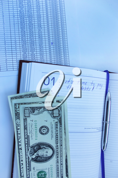 table with numerals, calculator, pen and american dollars