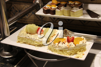 Cake with butter cream, berries and fruits, pineapple, strawberries and orange slices. Eating cakes decorated by strawberry and fruits. Enjoying sweet dish in restaurant. Dessert on plate