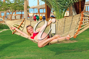 Attractive woman in swimsuit swaying in hammock enjoying summer holidays. Girl laying in hammock at tropical resort. Holidays during summer holidays. Enjoing relaxing. Lifestyle of modern woman
