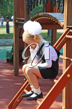 Schoolgirl is sad and sitting on playground. Offended child. The child does not want to go to school. Poor mood in child. Schoolgirl fell into thought. The first grader thought