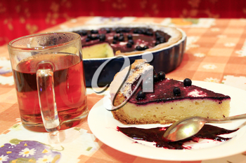 piece of fresh pie with bilberry on the plate and cup of tea