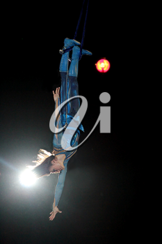 Circus number. Slender girl showing trick during performance of gymnasts in circus. Gymnast equilibrist under circus dome