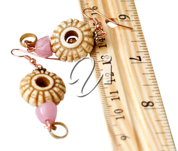 bone earrings and wooden rule isolated on white