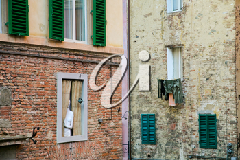 wall with windows and sculpture in old town (Siena, Italy)