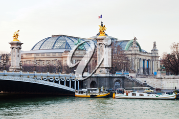Pont Alexandre III and Grand Palais in the background, in Paris evening