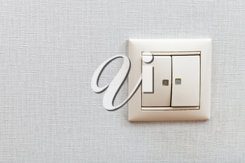 Wall-mounted light switch on room wall close up