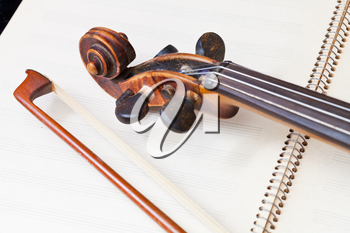 violin bow and scroll on music book close up