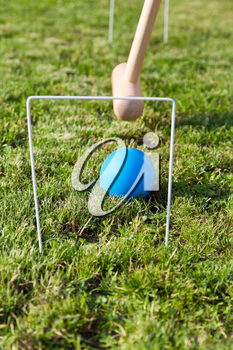 mallet and blue ball in game of croquet on green lawn in summer day