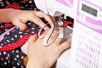 sewer sews clothes on sewing machine close up