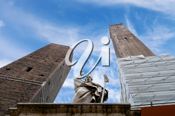 Two towers and the statue of Saint Petronius under blue sky in Bologna, Italy
