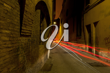 stone medieval street in Bologna and car red headlights at night, Italy