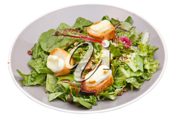 green salad with goat cheese and croutons on plate isolated on white background
