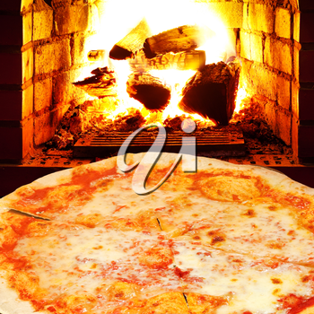 italian pizza margherita and open fire in wood burning stove