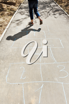 girl hops in hopscotch on urban alley in sunny day
