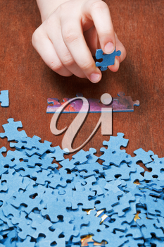 choosing of jigsaw puzzles on wooden table