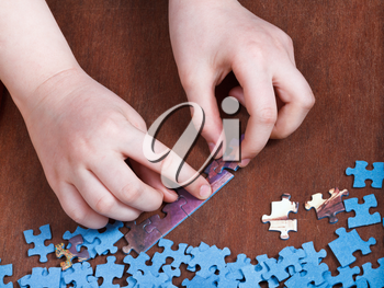linking of jigsaw puzzles on wooden table