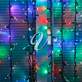 outdoor Christmas lamp strings decorate window in night