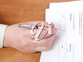 businessman signs a contract by silver pen on table