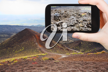 travel concept - tourist taking photo of craters volcano Etna on mobile gadget, Sicily, Italy