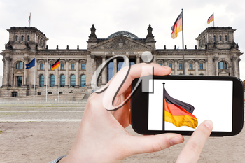 travel concept - tourist taking photo of Reichstag Building on mobile gadget, Berlin, Germany