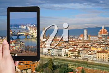 travel concept - tourist taking photo of Ponte Vecchio in Florence on mobile gadget, Italy