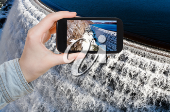 travel concept - tourist takes picture of river waterfall on Croton Dam in winter day on smartphone, USA