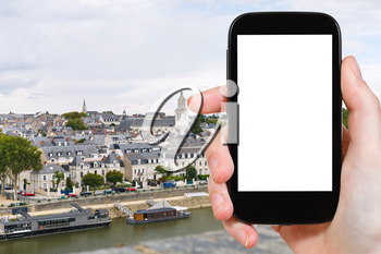 travel concept - tourist photograph quay des Carmes in Anges, France on smartphone with cut out screen with blank place for advertising logo