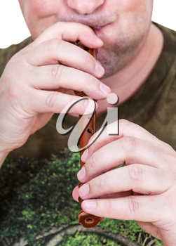 street musician with inflated cheeks plays flute close up