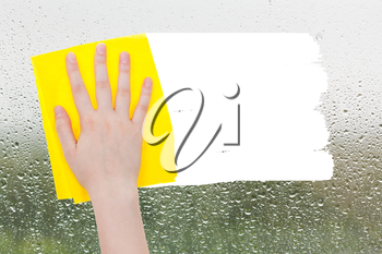 weather concept - hand deletes raindrops on glass by yellow rag from image and white empty copy space are appearing
