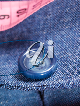 attaching of button to blue silk suit by needle close up