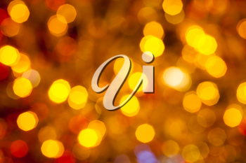 abstract blurred background - dark brown yellow and red shimmering Christmas lights bokeh of electric garlands on Xmas tree
