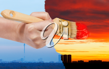 nature concept - seasons and weather changing: hand with paintbrush paints red sunset on blue sunrise