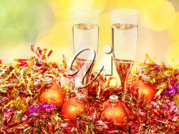 Christmas still life - two glasses of champagne at golden Xmas decorations with yellow and green blurred Christmas lights bokeh background