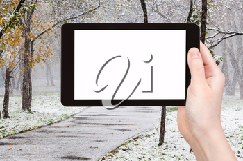 season concept - hand holds tablet pc with cut out screen and first snowfall in urban park on background