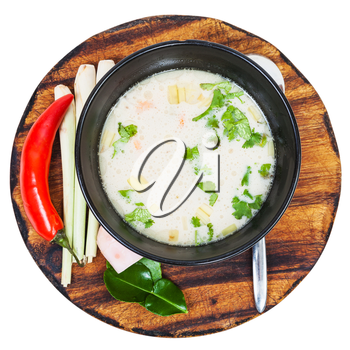 above view soup Tom yam nam khon made with shrimps, coconut milk, chilli pepper, lemongrass, galangal, coriander, kaffir lime leaves in bowl and ingredients on wood board isolated on white background