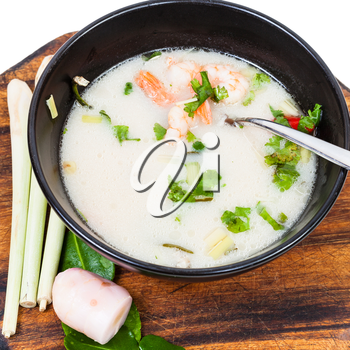 above view thai soup Tom yam nam khon made with shrimps, coconut milk, chilli pepper, lemongrass, galangal, coriander, kaffir lime leaves in bowl and ingredients on wooden board