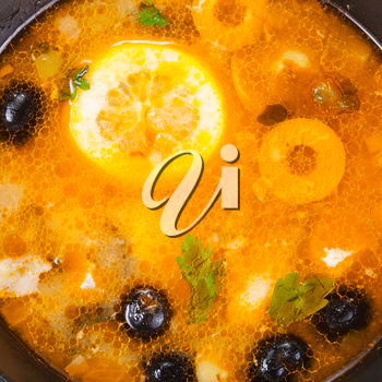 food background - Solyanka russian traditional spicy and sour soup with fish in bowl close up