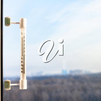outdoor thermometer with minus 25 degrees celsius temperature on window pane in cold winter day